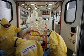 The medical team of the Paris emergency unit, wearing their protective suits, load a protective stretcher with a dummy inside into an ambulance for a training session to take care of suspected Ebola case during the presentation to the Press, in Paris, Friday, Oct. 24, 2014. (AP Photo/Francois Mori)