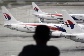 A man views a fleet of Malaysia Airline planes on the tarmac of the Kuala Lumpur International Airport, in Malaysia, Thursday, Jan. 29, 2015. Malaysia's Civil Aviation Authority officially declared the MH370 crash an accident on Thursday, fulfilling a legal obligation that will allow efforts to proceed with compensation claims. (AP Photo/Joshua Paul)