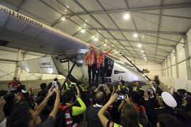 Pilots Andre Boschberg, center left, and Bertrand Piccard, at right, pose for photos with their solar powered plane in a hangar at Chongqing Jiangbei International Airport in southwest China's Chongqing Municipality, Tuesday, March 31, 2015. The Solar Impulse 2 landed in Chongqing early Tuesday after a 20-hour, 1,375-kilometer (854 mile) flight from Mandalay, Myanmar, on the fifth leg of the plane's attempt to circumnavigate the globe. (AP Photo) CHINA OUT