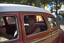 A woman waits in a classic American car that's used as a shared taxi by commuters in Havana, Cuba, early Thursday, Dec. 18, 2014. After a half-century of Cold War acrimony, the United States and Cuba abruptly moved on Wednesday to restore diplomatic relations _ a historic shift that could revitalize the flow of money and people across the narrow waters that separate the two nations. (AP Photo/Ramon Espinosa)