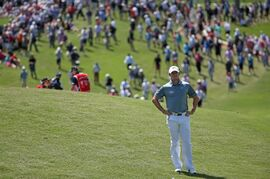 Northern Ireland's Rory McIlroy waits to play on the 10th fairway as a crowd gathers behind him during the second round of the Australian Open Golf championship in Sydney, Friday, Nov. 28, 2014. (AP Photo/Rick Rycroft)