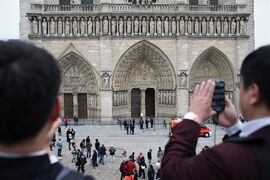 Tourists take pictures as police officers stand guard in front of Notre Dame Cathedral, in Paris, Tuesday, May 21, 2013. Notre Dame has been evacuated after a man committed suicide in the 850-year-old monument and tourist attraction. (AP Photo/Thibault Camus)
