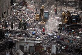 FILE - In this Sunday, May 12, 2013 file photo, Bangladeshi rescuers use heavy machinery to clear rubble of a garment factory building that collapsed on April 24 as they continue searching for bodies in Savar, near Dhaka, Bangladesh. A government investigation said poor quality construction materials and building code violations contributed to the collapse of building housing garment factories last month in Bangladesh. (AP Photo/A.M. Ahad, File)