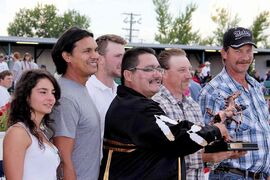 Actor Adam Beach (second from left) and Peguis Chief Glenn Hudson (holding trophy) make the winner's circle presentation on Labour Day.