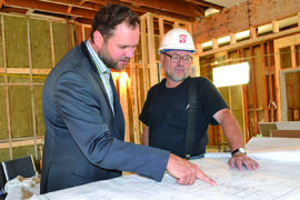 Matt Wiebe, MLA for Concordia, and Richard Grewe of Gardon Construction, examine the plans for the new 41-space childcare centre coming to Sherwood School.
