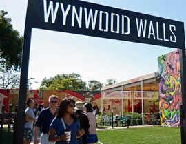 This April 4, 2015 photo shows people walking through Wynwood Walls, a complex of restaurants and art galleries that feature a rotating roster of prominent street artists in Miami's Wynwood neighborhood. (AP Photo/Jennifer Kay)