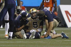 Winnipeg Blue Bombers QB Drew Willy is checked by medical staff after getting injured against the B.C. Lions on Saturday night at B.C. Place.