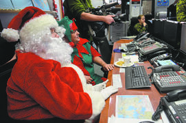 Santa and his elf, Eugene, enjoy some milk and cookies during a pre-flight briefing at the Canadian NORAD Region headquarters.