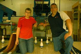 Rossmere Lanes owner Jamie Newton (right) and crew member Adam Dubinsky are shown in front of one of the string pin-setting machines at the alley.