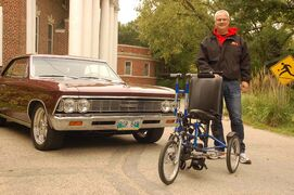 Manitoba Street Rod Association past president Chris Jelfs stands in front of his 1966 Chevrolet Chevelle with a special bike for a Rehabilitation Centre for Children user.