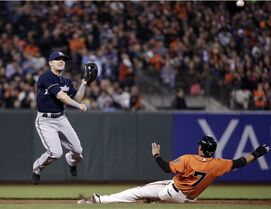 Milwaukee Brewers second baseman Scooter Gennett, left, turns a double play over San Francisco Giants' Gregor Blanco on a ground ball by Brandon Crawford during the first inning of a baseball game on Friday, Aug. 29, 2014, in San Francisco. (AP Photo/Marcio Jose Sanchez)