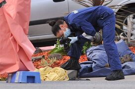 A forensic officer documents objects including a blanket at the scene of a fatal shooting at Endeavour Hills Police Station in Melbourne, Wednesday, Sept. 24, 2014. A suspected terrorist was shot dead and two counterterrorism police were stabbed Tuesday in a confrontation in Australia's second largest city that some experts suspect is inspired by the Islamic State group's call to supporters to wage terror in their home countries. (AP Photo/AAP Image, Julian Smith) AUSTRALIA OUT, NEW ZEALAND OUT, PAUPAU NEW GUINEA OUT, SOUTH PACIFIC OUT, NO SALES, NO ARCHIVING