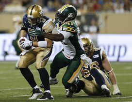 Bombers quarterback Drew Willy was under fire all night from the Edmonton Eskimos defence. Here, he gets hauled down by Odell Willis.