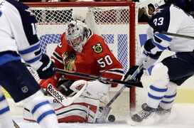 Chicago goalie Corey Crawford shuts the door on Winnipeg blue-liner Dustin Byfuglien (33) during first-period action Wednesday.