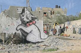 A Palestinian woman works with her children near a mural of a playful-looking kitten, presumably painted by British street graffiti artist Banksy, is seen on a wall.