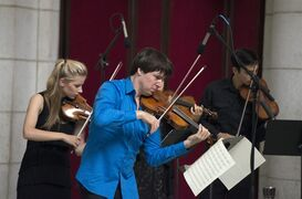 Acclaimed violinist Joshua Bell performs with young musicians who are alumni of the National YoungArts Foundation (YoungArts) during a performance, Tuesday, Sept. 30, 2014, at Union Station in Washington. Seven years ago, Bell performed incognito for tips in a Washington subway station, but almost no one stopped to listen. The subway performance was an experiment with The Washington Post to see if anyone would notice some of the world's great music during their rush to work. It made for a good story that eventually won the Pulitzer Prize and inspired a children's book and even mentions in church sermons. (AP Photo/Molly Riley)
