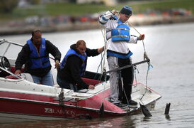 Kyle Kematch grapples with a tree trunk tangled in a drag-line behind a motor boat Wednesday as a search for missing and murdered aboriginal women got underway in Winnipeg. Kematch's sister is one of the missing.