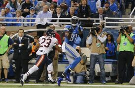 Detroit Lions wide receiver Calvin Johnson (81), defended by Chicago Bears cornerback Kyle Fuller (23), pulls in a 6-yard pass for a touchdown during the first half of an NFL football game in Detroit, Thursday, Nov. 27, 2014. (AP Photo/Paul Sancya)