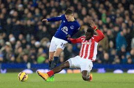 Everton's John Stones, left, and Stoke City's Mame Biram Diouf battle for the ball, during the English Premier League match between Everton and Stoke City, at Goodison Park, in Liverpool, England, Friday Dec. 26, 2014. (AP Photo/PA, Lynne Cameron) UNITED KINGDOM OUT NO SALES NO ARCHIVE