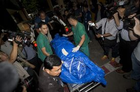 The body of slain British tourist, David Miller, wrapped in plastic sheet, is carried at a forensic police facility in Bangkok, Thailand, Tuesday, Sept. 16, 2014. Police on the scenic resort island of Koh Tao in southern Thailand conducted a sweep of hotels and workers' residences Tuesday searching for clues into the slayings of two British tourists whose nearly naked, battered bodies were found on a beach a day earlier.(AP Photo/Sakchai Lalit)