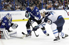 Winnipeg Jets winger Chris Thorburn (right) shoots on Tampa Bay Lightning goalie Anders Lindback (left) as Lightning defenceman Matt Carle moves in during the first period.