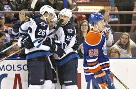 Winnipeg Jets' Blake Wheeler (26), Drew Stafford (12) and Mark Scheifele (55) celebrate a goal as Edmonton Oilers' Andrew Miller (58) skates past during first period NHL hockey action in Edmonton, Alta., on Monday.