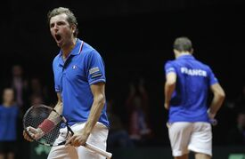 France's Julien Benneteau, left, reacts with Richard Gasquet while playing Switzerland's Stanislas Wawrinka, and Roger Federer during their doubles match for the Davis Cup final in Lille, northern France, Saturday, Nov.22, 2014. (AP Photo/Christophe Ena)