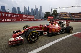 Ferrari driver Fernando Alonso of Spain steers his car during the first practice session for the Singapore Formula One Grand Prix on the Marina Bay City Circuit in Singapore, Friday, Sept. 19, 2014. In the background, the Singapore financial skyline is seen. (AP Photo/Ng Han Guan)