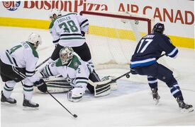 Winnipeg Jets Adam Lowry (#17) misses out on a first-period shot against Dallas Stars goaltender Kari Lehtonen (#32) during Saturday's game.