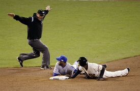 San Francisco Giants' Joaquin Arias is safe at second by umpire Jeff Nelson on a throw by Kansas City Royals' catcher Salvador Perez to Alcides Escobar, center, during the sixth inning of Game 4 of baseball's World Series Saturday, Oct. 25, 2014, in San Francisco. (AP Photo/Charlie Riedel)