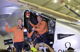 In this March 31, 2015 photo, Swiss pilots Andre Boschberg, left, and Bertrand Piccard stand in the cockpit of their solar powered plane after it touched down at Chongqing Jiangbei International Airport in southwestern China's Chongqing Municipality. Borschberg said Sunday, May 3, 2015 that he is anxious but excited about flying the Solar Impulse 2 solo from China to Hawaii on the longest leg of the first attempt to fly around the world without using a drop of fuel. (Chinatopix via AP) CHINA OUT