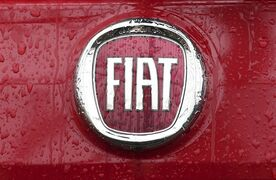 FILE - In this Thursday, Jan. 2, 2014 file photo, rain falls on a Fiat logo pictured on a car in Milan, Italy. Italian carmaker Fiat SpA, which controls Chrysler, says its second-quarter profits dropped by more than a half due to lower performance in North and Latin America. Fiat said Wednesday, July 30, 2014, that net profit was 197 million euros ($263 million), compared with 435 million euros in the same period last year. North American volumes were up 10 percent, driven by incentives to dealers to sell legacy Chrysler vehicles, but the incentives also cut into profits. Earnings before interest and tax in the region dropped 18 percent to 598 million euros. In Latin America, revenues dropped 13 percent as vehicle shipments fell 21 percent. Fiat said revenues in the quarter rose to 23.3 billion euros, up 1 billion euros over the same quarter last year. Fiat is currently finalizing its merger with Chrysler. (AP Photo/Antonio Calanni, File)