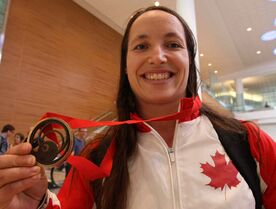 Marie-Josée Arès-Pilon shows off the bronze medal she won at the Commonwealth games in Glasgow in the 69 kilogram weight class in weightlifting.