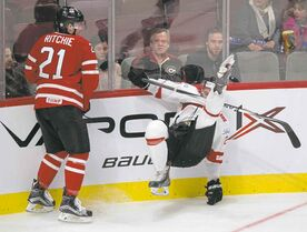 Switzerland's Simon Kindschi is checked into the boards by Nick Ritchie.