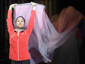 Yoshiko Kamikusa strides onto stage during the set-up for a performance of