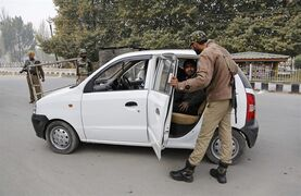 An Indian policeman checks passengers inside a car in Srinagar, India, Thursday, Oct. 23, 2014. Shops and businesses remained closed in Kashmir due to a separatist sponsored strike to protest a visit to the region by Prime Minister Narendra Modi. (AP Photo/Mukhtar Khan)