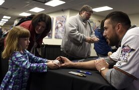 Minnesota Twins' Trevor Plouffe, right, signs an autograph during the baseball team's TwinsFest on Friday, Jan. 23, 2015, in Minneapolis. (AP Photo/Hannah Foslien)