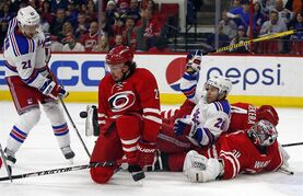 New York Rangers' Derek Stepan (21) battles Carolina Hurricanes' Justin Faulk (27) for the puck in front of teammate Martin St. Louis (26), Hurricanes goalie Cam Ward (30) and Andrej Sekera (4) of Slovakia, who are piled in front of the net during the first period of an NHL hockey game in Raleigh, N.C., Saturday, Dec. 20, 2014. (AP Photo/Karl B DeBlaker)