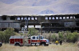 FILE - In this June 24, 2011 file photo, burned Amtrak passenger cars are left after the train was struck by a semitrailer near Fallon, Nev. A federal jury in Reno on Wednesday, Sept. 17, 2014 awarded $4.5 million to Amtrak and $210,777 to Union Pacific Railroad for damages resulting from John Davis Trucking Co.'s negligence when one of its trucks slammed into the side of the passenger train. U.S. District Judge Howard McKibben has put the judgment on hold until Sept. 29 to consider adding up to another $1 million or more in attorney fees and interest to the award to the railroad companies. (AP Photo/Reno Gazette Journal, Liz Margerum, File)