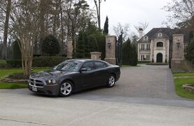 A car carrying Minnesota Vikings head coach Mike Zimmer and general manager Rick Spielman leaves the home of NFL running back Adrian Peterson, Wednesday, March 4, 2015. in The Woodlands, Texas. Zimmer and Spielman met with Peterson to discuss his future with the NFL football team. (AP Photo/Conroe Courier, Jason Fochtman)