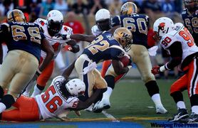 B.C. Lions players close in on Winnipeg's Fred Reid on Thursday night.