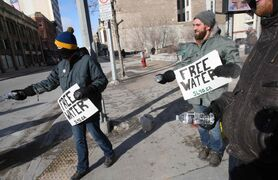 Chuck Wright (right) and other concerned citizens hand out bottles of water with a statement on the long boil-water advisory in Shoal Lake 40 First Nation.