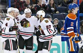 Chicago Blackhawks' Niklas Hjalmarsson (4), Jonathan Toews (19), Marian Hossa (81) and Johnny Oduya (27) celebrate a goal as Edmonton Oilers' Jeff Petry (2) skates past during first period NHL hockey action in Edmonton, on Saturday November 22, 2014. THE CANADIAN PRESS/Jason Franson