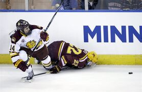 Minnesota Duluth's Alex Iafallo (14) collides with Minnesota's Travis Boyd (22) as they chase the puck along the boards in the first period of an NCAA college hockey regional semifinal game in Manchester, N.H., Friday, March 27, 2015. (AP Photo/Elise Amendola)