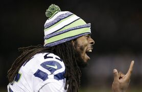 FILE - In this Aug. 28, 2014, file photo, Seattle Seahawks cornerback Richard Sherman yells on the sideline during the second half of an NFL preseason football game against the Oakland Raiders in Oakland, Calif. � The places and ways to escape were simpler not long ago. Back then, Richard Sherman's dreadlocks might bring a curious glance but they would be quickly forgotten. (AP Photo/Marcio Jose Sanchez, File)