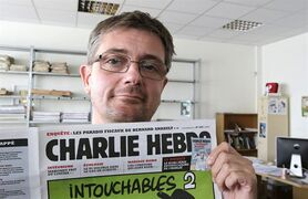 FILE - In this Sept.19, 2012 file photo, Stephane Charbonnier also known as Charb , the publishing director of the satyric weekly Charlie Hebdo, displays the front page of the newspaper as he poses for photographers in Paris. The late former editor of French weekly Charlie Hebdo takes on politicians, the media and