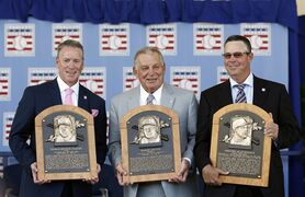 National Baseball Hall of Fame inductees Tom Glavine, left, Bobby Cox and Greg Maddux, right, hold their plaques after an induction ceremony at the Clark Sports Center on Sunday in Cooperstown, N.Y.