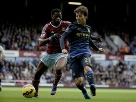 West Ham's Alex Song, left, competes for the ball with Manchester City's David Silva during the English Premier League soccer match between West Ham and Manchester City at Upton Park stadium in London, Saturday, Oct. 25, 2014. (AP Photo/Matt Dunham)