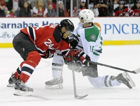 New Jersey Devils' Bryce Salvadore, left, checks Dallas Stars' Ryan Garbutt during the first period of an NHL hockey game Friday, Oct. 24, 2014, in Newark, N.J. (AP Photo/Bill Kostroun)