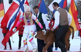 Lindsey Vonn, of United States, left, leads a calf as she celebrates after winning an alpine ski women's World Cup downhill in Val d'Isere, France, Saturday, Dec. 20, 2014. (AP Photo/Giovanni Auletta)